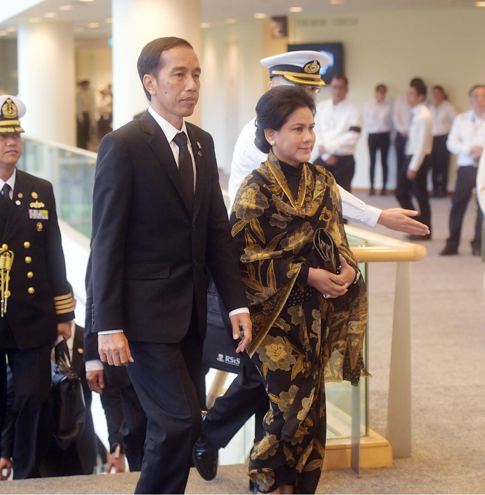 In this Sunday, March 29, 2015, photo, Indonesia President Joko Widodo, second left, accompanied by his wife Iriana, right, arrives at the state funeral for the late Lee Kuan Yew at the University Cul