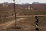 In this April 17, 2011 photo, people go about their daily routines south of Pyongyang along the highway leading to the southern city of Kaesong, North Korea. (AP Photo/David Guttenfelder)