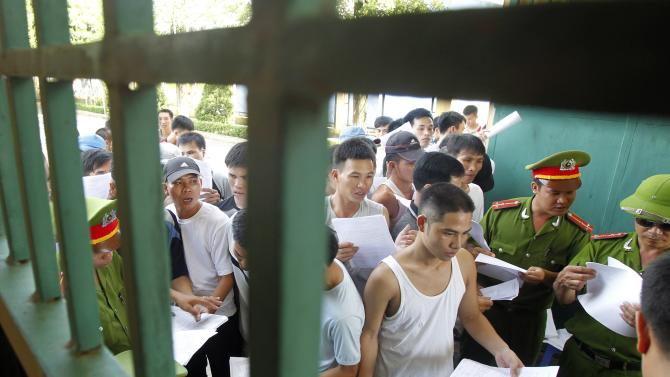 Freed inmates walk past uniformed policemen while they are being released from Hoang Tien prison outside Hanoi