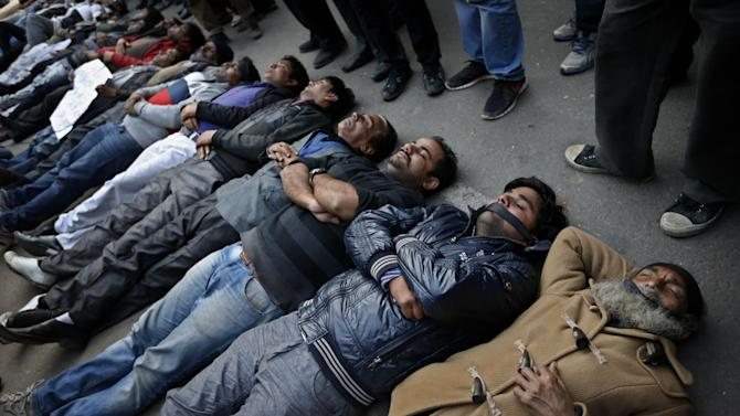 Indian men and women lie down on the ground mimicking dead bodies as they mourn the death of a gang rape victim in New Delhi, India, Saturday, Dec. 29, 2012. Shocked Indians on Saturday were mourning the death of the woman who was gang-raped and beaten on a bus in New Delhi nearly two weeks ago in an ordeal that galvanized people to demand greater protection for women from sexual violence. (AP Photo/ Saurabh Das)