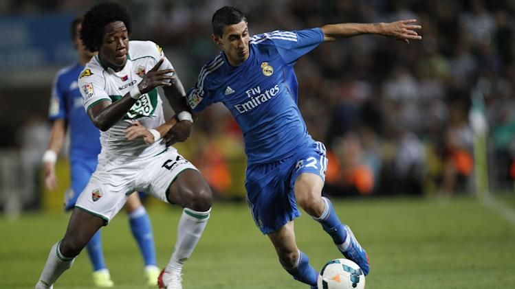 Real Madrid's Angel Di Maria from Argentina, right, duels for the ball with Elche's  Carlos Alberto Sanchez Moreno, left,  during their La Liga soccer match at the Martinez Valero stadium in Elche, Spain, Wednesday, Sept. 25, 2013