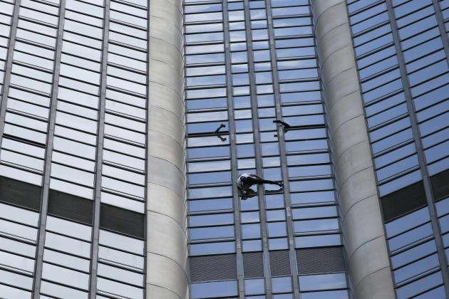 """People take pictures from the window as French climber Alain Robert, also known as """"Spiderman"""", scales the Tour Montparnasse, a 210-metre (689 ft) building in central Paris"""