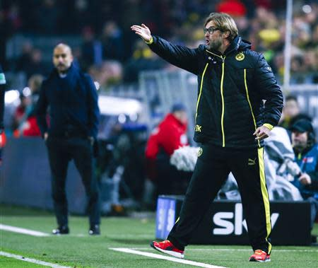 Borussia Dortmund's coach Klopp reacts next to Bayern Munich's coach Guardiola during their German first division Bundesliga soccer match in Dortmund