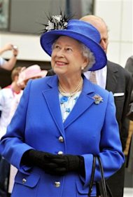 Queen Elizabeth II smiles as she meets one of the members of Britain's Olympic team, as she and the Duke of Edinburgh tour the Athletes Village at th