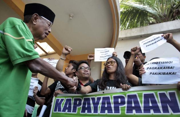 Sultan of Sulu Jamalul Kiram III (L) greets artist/comedian Arvin Jimenez, also known as Tado, who is with the group Patriyotikong Pilipino (Filipino patriots) during a rally showing support for the Kirams, in Maharlika Village, Taguig City, south of Manila, on 06 March 2013. Malaysian authorities yesterday launched a large-scale operation against supporters of Sultan Kiram encamped in Lahad Datu, Sabah, that has left at least 27 people dead. (Mike Alquinto/NPPA Images)
