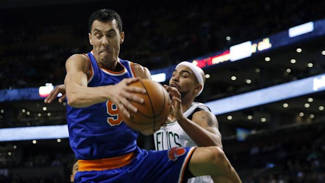 New York Knicks guard Pablo Prigioni (9) pulls down a rebound in front of Boston Celtics guard Jerryd Bayless during the second half of an NBA basketball game in Boston, Wednesday, March 12, 2014. The Knicks won 116-92