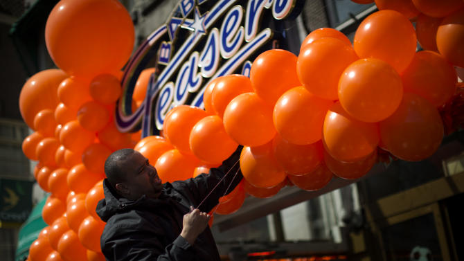 A man sets up decorations in the Dutch national colors of orange in downtown Amsterdam, Netherlands Monday, April 29, 2013. Queen Beatrix has announced she will relinquish the crown on April 30, 2013, after 33 years of reign, leaving the monarchy to her son Crown Prince Willem Alexander. (AP Photo/Emilio Morenatti)