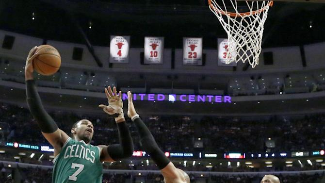Boston Celtics power forward Jared Sullinger (7) shoots over Chicago Bulls power forward Carlos Boozer, center, and Taj Gibson (22) during the second half of an NBA basketball game on Thursday, Jan. 2, 2014, in Chicago. The Bulls won 94-82