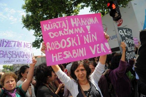 """A Turkish feminist (right) holds a placard reading """"Don't touch our abortion rights"""" during a protest outside Prime Minister Recep Tayyip Erdogan's office in Istanbul on May 27. Some 300 women are to protest to the Turkish government Tuesday after Erdogan sparked fury among women's rights advocates by likening abortion to murder."""
