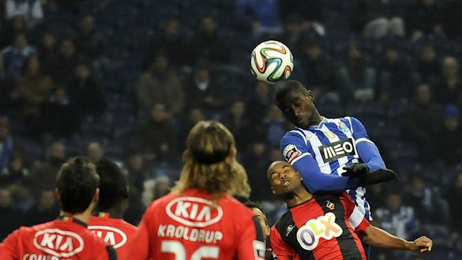 FC Porto's Jackson Martinez, from Colombia, jumps higher to score his teams second goal past Olhanense's Pedro Celestino, second right, in a Portuguese League soccer match at the Dragao Stadium in Porto, Portugal, Friday, Dec. 20, 2013