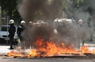 """German police men stand behind a burning barricade during a rally against a """"Day of German Future"""" demonstration by far-right extremists in Hamburg on June 2. German police said 38 officers were injured in violent clashes between neo-Nazi demonstrators and far-left counter-protesters"""