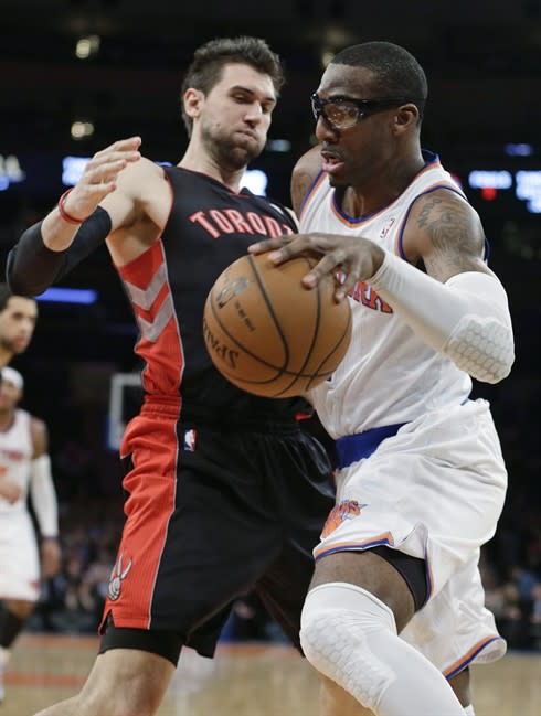 New York Knicks' Amar'e Stoudemire, right, drives past Toronto Raptors' Andrea Bargnani during the first half of an NBA basketball game Wednesday, Feb. 13, 2013, in New York.(AP Photo/Frank Franklin II)