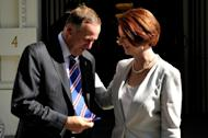 This file photo shows New Zealand's Prime Minister John Key showing his tie to his Australian counterpart Julia Gillard, in Melbourne, on January 29, 2012. New Zealand is to accept 150 refugees a year from Australia, Key said on Saturday, to ease pressure on Canberra which is grappling with a surge in boatpeople heading to the region