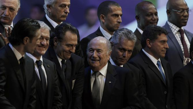 Blatter prepares to pose for a group picture during the draw for the 2014 World Cup in Sao Joao da Mata