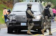 Mexican soldiers walk past a US diplomatic vehicle on the Tres Marias-Huitzilac highway in Morelos, Mexico, August 24. Mexican federal police shot at the US diplomatic car as they chased criminals south of Mexico City, in a chaotic incident that left two US embassy employees wounded