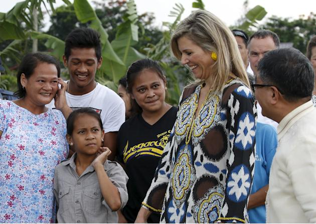 Queen Maxima of the Netherlands, the UN Secretary-General's Special Advocate for Inclusive Finance for Development, talks to a Filipino family at a pineapple farm in Tagaytay city