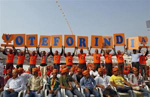 Supporters of Narendra Modi, the prime ministerial candidate for Bharatiya Janata Party, hold placards during a rally in Ahmedabad