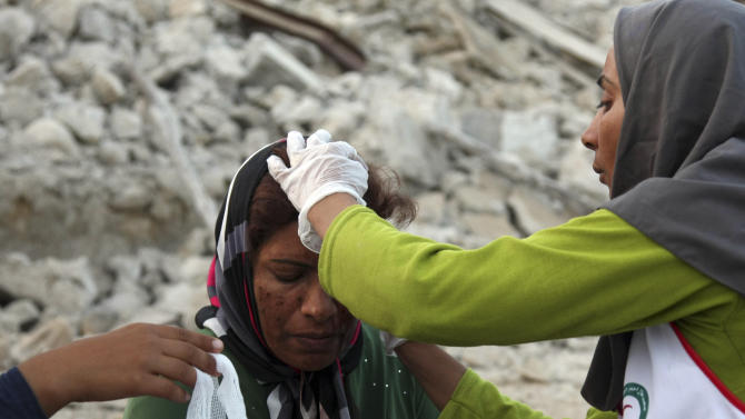 An Iranian woman receives medical treatment after an earthquake struck southern Iran, in Shonbeh, Iran, Tuesday, April 9, 2013. A 6.1 magnitude earthquake killed dozens and injured hundreds more in a sparsely populated area in southern Iran on Tuesday, Iranian officials said, adding that it did not damage a nuclear plant in the region. (AP Photo/Fars News Agency, Mohammad Fatemi)