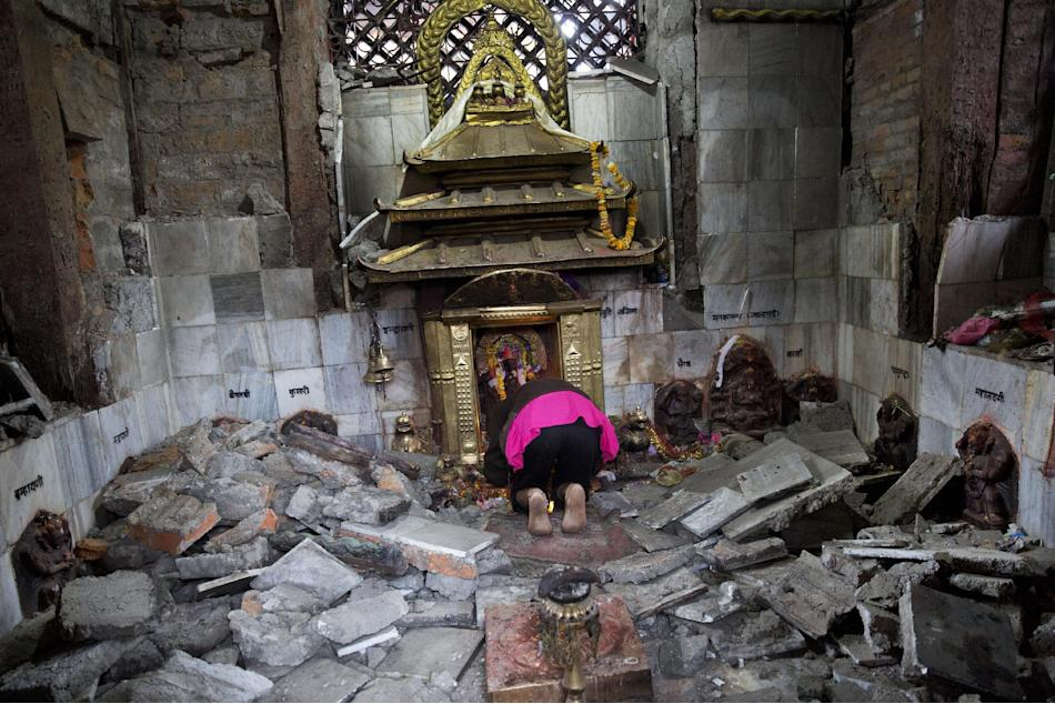 A Hindu Nepalese woman offers prayers at Indrayani temple, that was damaged in Saturday's earthquake, in Kathmandu, Nepal, Monday, April 27, 2015. A strong magnitude earthquake shook Nepal's capital a