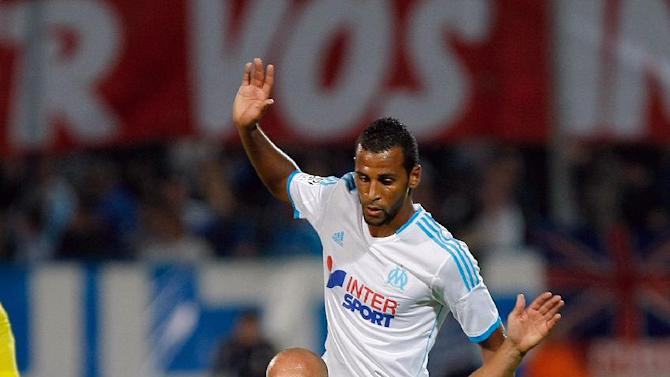 Saint-Etienne's French midfielder Renaud Cohade, front, and Marseille's Togolese midfielder Jacques-Alaixys Romao battle for the ball during their League One soccer match, at the Velodrome Stadium, in Marseille, southern France, Tuesday, Sept. 24, 2013