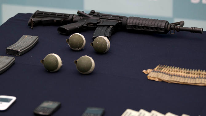 "Confiscated money, grenades, and guns are displayed during the media presentation of the alleged leader of a faction of the hyper-violent Zetas cartel, Ivan Velazquez Caballero, known as ""El Taliban,"" at the Mexican Navy's Center for Advanced Naval Studies in Mexico City,Thursday, Sept. 27, 2012. Velazquez Caballero allegedly has been fighting a bloody internal battle with top Zetas' leader Miguel Angel Trevino Morales, and officials have said the split was behind a recent surge in massacres and shootouts, particularly in northern Mexico. (AP Photo/Eduardo Verdugo)"