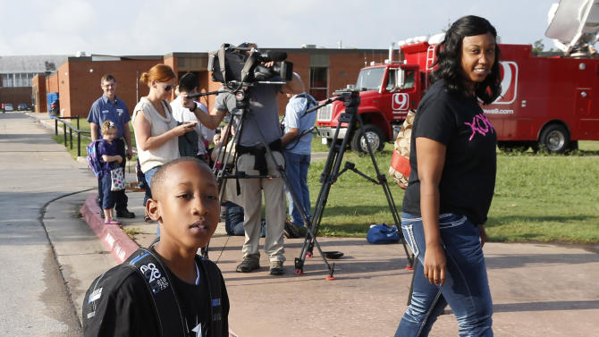 Cam'ron Richardson, left, walks past reporters, rear, with his mother, Alicia Richardson, right, as he arrives for the first day of school at Plaza Towers Elementary school in their temporary location at Central Jr. High school in Moore, Okla., Friday, Aug. 16, 2013. The Briarwood and Plaza Towers elementary schools were destroyed when an EF5 twister hit Moore on May 20. Cam'ron was trapped under the rubble of the tornado that killed two dozen people. (AP Photo/Sue Ogrocki)