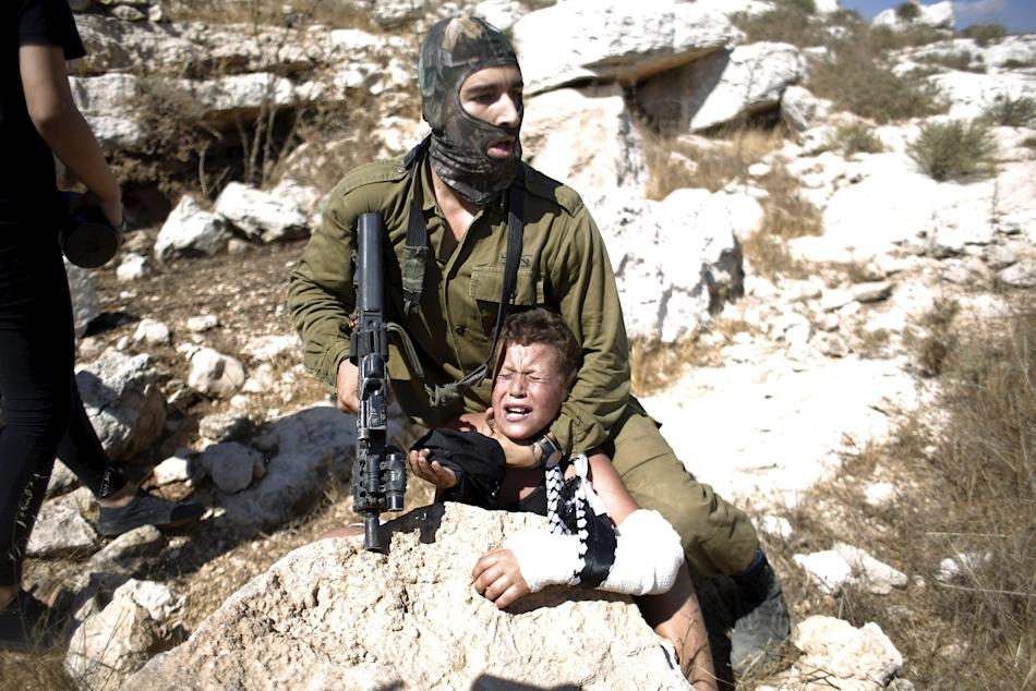 An Israeli soldier detains a Palestinian boy during a protest against Jewish settlements in the West Bank village of Nabi Saleh near Ramallah
