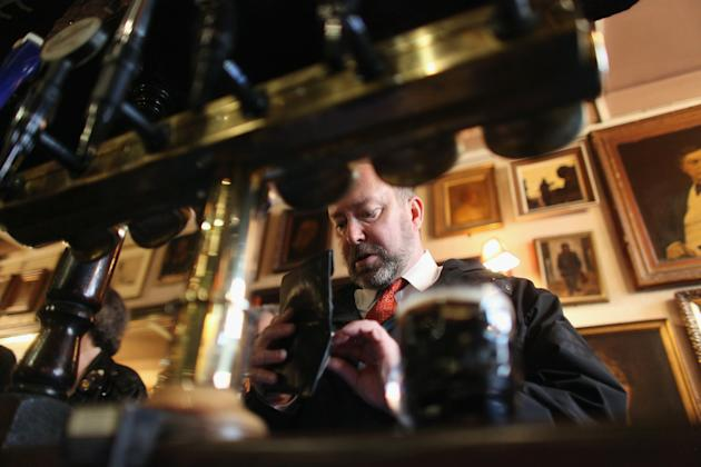 """LONDON, ENGLAND - FEBRUARY 16: A man checks his wallet as he buys a pint in The Harp pub on the day it was named as the Campaign for Real Ale's national pub of the year on February 16, 2011 in London, England. It is the first time that a London pub has been awarded the the prestigious title of CAMRA pub of the year. The Harp, which is owned by real ale pioneer Bridget Walsh, is situated yards from Trafalgar Square and Covent Garden. CAMRA commented that the pub """"retains its appeal as a true local, even though situated in the tourist heart of the capital"""". (Photo by Oli Scarff/Getty Images)"""
