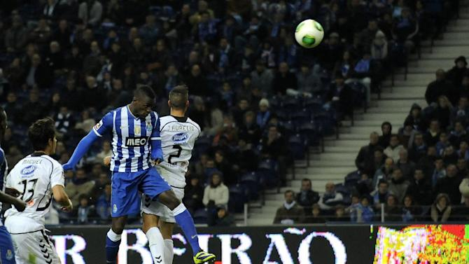FC Porto's Jackson Martinez, from Colombia, scores the opening goal past Nacional's Joao Aurelio, right, in a Portuguese League soccer match at the Dragao stadium in Porto, Portugal, Saturday, Nov. 23, 2013