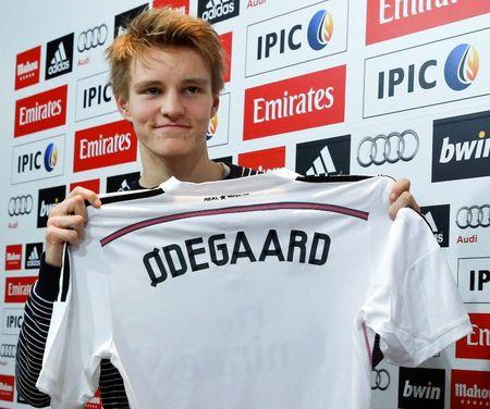 Real Madrid's new teenage signing Martin Odegaard from Norwegian club Stromsgodset holds up his jersey during his presentation at the Valdebebas training grounds in Madrid