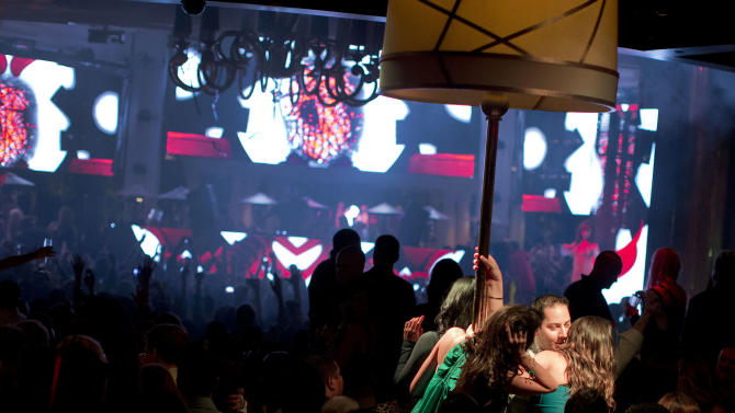With a private table spotlighted, right, revelers dance to the music played by DJ Afrojack inside the XS nightclub in Las Vegas on Sunday, Jan. 20, 2013. (AP Photo/Julie Jacobson)