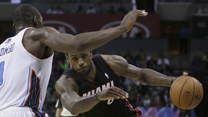 Miami Heat's LeBron James, right, looks to drive past Charlotte Bobcats' Bismack Biyombo, left, during the second half of an NBA basketball game in Charlotte, N.C., Saturday, Nov. 16, 2013. Miami won 97-81