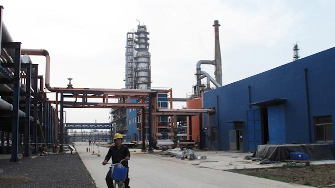An employee rides a bike on a road near refinery plants of Chambroad Petrochemicals, in Boxing
