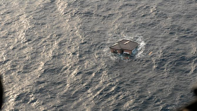 FILE - This file photo taken March 13, 2011, and provided by the U.S. Navy, shows a Japanese home adrift in the Pacific Ocean, days after a massive earthquake and the ensuing tsunami hit Japan's east coast. Scientists believe ocean waves carried away 3-4 million tons of the 20 million tons of debris created by tsunamis that slammed into Japan after a magnitude-9.0 earthquake nearly a year ago. One-to-two million tons of it _ lumber and other construction material, fishing boats and other fragments of coastal towns _ are still in the water and are being carried across the Pacific by ocean currents. One to five percent of that may reach coastlines in Hawaii, Alaska, Oregon and Washington states. (AP Photo/U.S. Navy, Dylan McCord)