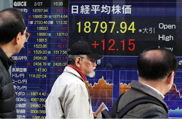 People watch an electronic stock board of a securities firm in Tokyo Friday, Feb. 27, 2015. Asian stocks were lackluster Friday after U.S. markets drifted lower and Japan reported faster growth in fac