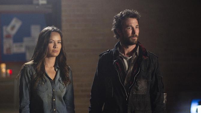 """In this undated photo released by TNT, actors, Moon Bloodgood, left, and Noah Wyle, appear in a scene from TNT's """"Falling Skies"""" Season Finale - Part 1: """"Mutiny."""" Wyle is confronting an alien invasion, the death of his wife and the potential annihilation of the human species in the new season of """"Falling Skies,"""" which debuts Sunday, June 17, 2012, 9-11 p.m. EDT on TNT.  (AP Photo/TNT, Ken Woroner)"""