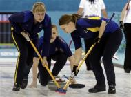 Sweden's Christina Bertrup (C) delivers a stone as teammates vice Maria Prytz (L) and Maria Wennerstroem sweep the ice during their women's curling semifinal game against Switzerland at the 2014 Sochi Winter Olympics in the Ice Cube Curling Center in Sochi February 19, 2014. REUTERS/Ints Kalnins