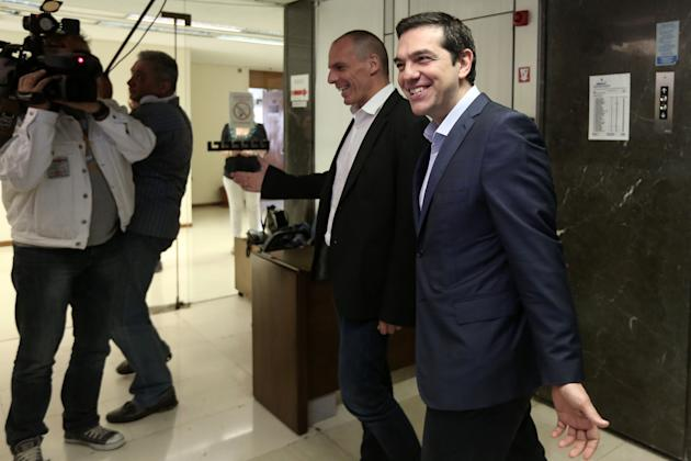 Greece's Prime Minister Alexis Tsipras, right, is welcomed by Finance Minister, Yanis Varoufakis, during his visit at the Finance Ministry in Athens Wednesday, May 27, 2015. Greece is out of cash