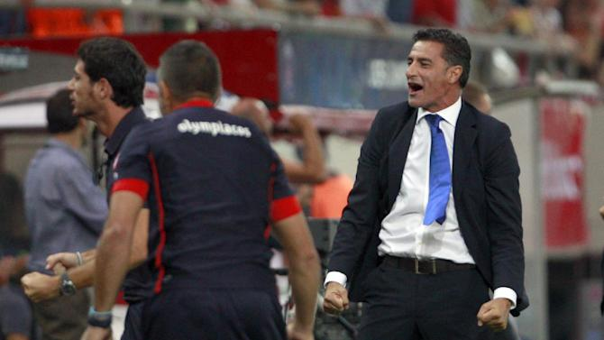 Olympiacos' coach Michel, celebrates a goal, during the soccer Champions League group C match between Olympiakos and Paris Saint Germain in Piraeus, Greece, Tuesday, Sept. 17, 2013