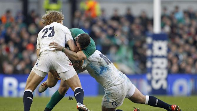 Ireland's Robbie Henshaw, centre, is tackled by England's Billy Twelvetrees, left, and England's Tom Youngs rugby union 6 nations match at the Aviva stadium, Dublin, Ireland, Sunday, March, 1, 2015.  (AP Photo/Peter Morrison)
