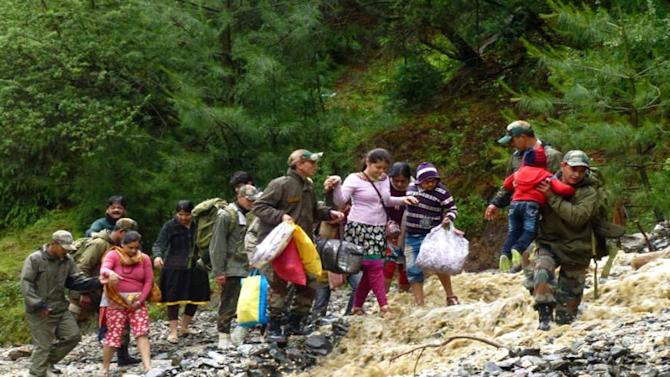 In this Tuesday June 18, 2013 photo, released by Indian army, Indian army soldiers help stranded people to reach at safer place in Uttarkashi, in northern Indian state of Uttrakhund. India's army and air force evacuated nearly 12,000 Hindu pilgrims stranded in a mountainous area after torrential monsoon rains and landslides caused death and destruction in northern India. At least 69 people died and 63,000 people remain stranded. (AP Photo/Indian Army)