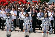 Mission commander Jing Haipeng (R) with fellow astronauts Liu Wang (C) and Liu Yang, China's first female astronaut, wave to the crowd prior to boarding the Shenzhou-9 spacecraft on June 16. The crew's main task during their 13-day mission is to carry out China's first manual space docking