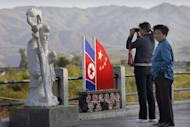 Chinese visitors look towards North Korea across the border with China in Jilin province. The Yomiuri Shimbun quoted two Chinese officials as saying the long-standing policy of swiftly returning any North Korean who made it across the border and into China -- despite the punishment they face -- had been put on hold
