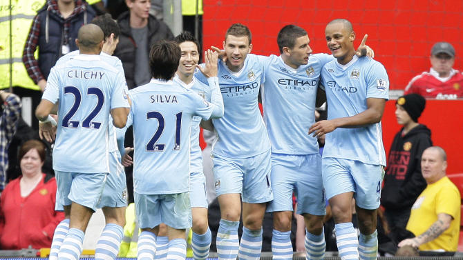 Manchester City's Edin Dzeko, centre right, celebrates with teammates after his second goal during his team's 6-1 win over Manchester United in their English Premier League soccer match at Old Trafford Stadium, Manchester, England, Sunday Oct. 23, 2011. (AP Photo/Jon Super)