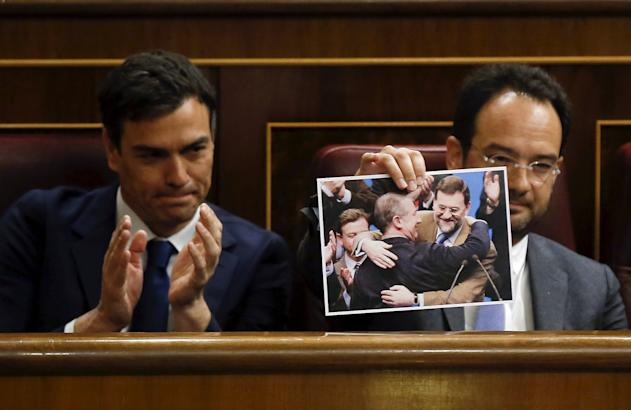 Antonio Hernando, parliament spokesman of Spain's opposition Socialist Party (PSOE), holds up a picture of Spain's Prime Minister Mariano Rajoy embracing former International Monetary Fund chief Rodrigo Rato, next to PSOE leader Pedro Sanchez (L) during a government control session at Spain's Parliament in Madrid, April 22, 2015. REUTERS/Andrea Comas