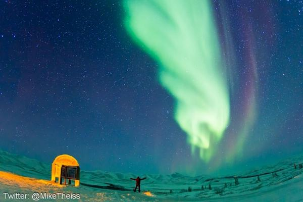 National Geographic photographer Mike Theiss taking in the northern lights. The sign denoting the edge of the Arctic Circle can be seen to the left.