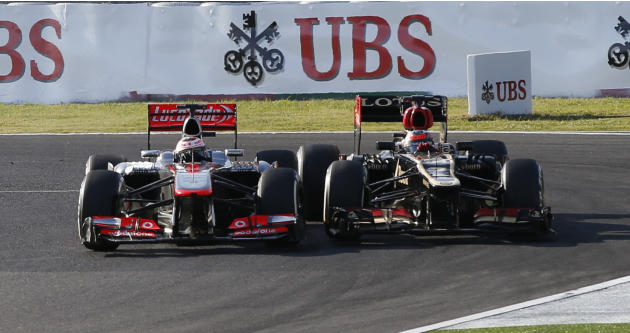 McLaren Formula One driver Button of Britain and Lotus Formula One driver Raikkonen of Finland fight for position during the Japanese F1 Grand Prix at the Suzuka circuit