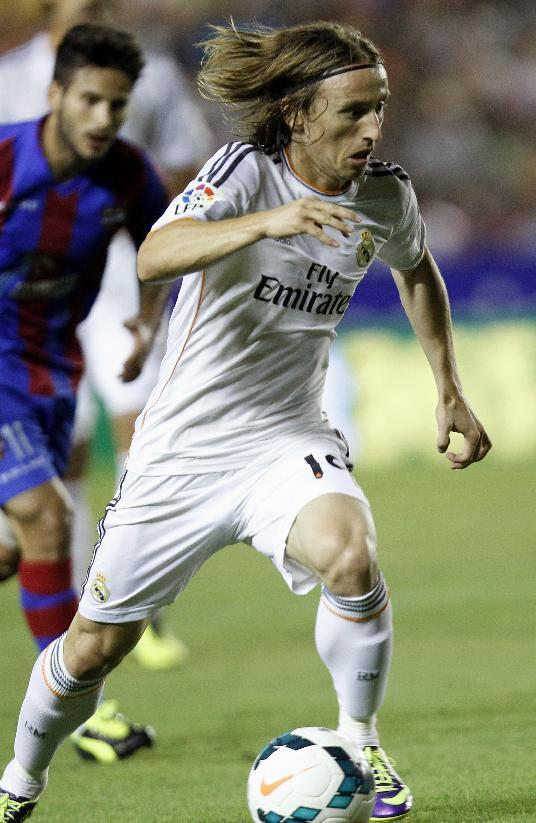 Real Madrid's Luka Modric from Croatia drives the ball followed by Levante's Ruben Garcia during their La Liga soccer match at the Ciutat de Valecia stadium in Valencia, Spain, Saturday, Oct. 5, 2013
