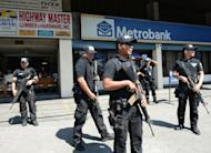 Members of the Pasay City SWAT team patrol in front of a bank in Manila on February 1, 2013. Five young men were shot dead before dawn on Wednesday in a street on the outskirts of the Philippines' main business district, police said