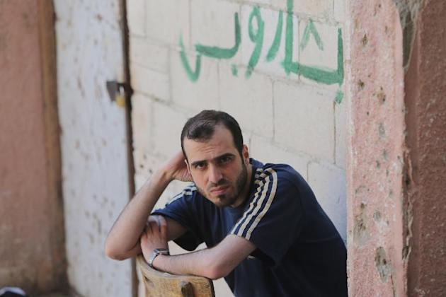 """A Syrian rebel fighter who surrendered to the government during the siege of Homs sits in front of graffiti reading in Arabic """"Bashar [al-Assad], nothing else"""" at the Al-Andalous school turned into a detention center on May 13, 2014"""